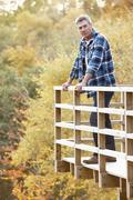 man standing on wooden balcony overlooking autumn woodland - stock photo