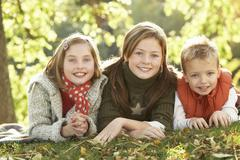 Group of 3 children realxing outdoors in autumn landscape Stock Photos