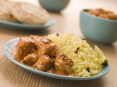 Plated Chicken Korma with Pilau Rice and Naan bread Stock Photos