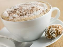 Cup of Cappucino with an Amaretti Biscuit - stock photo