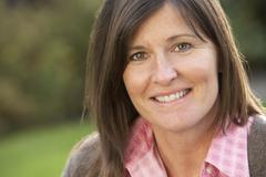 close up portrait of smiling brunette woman outdoors - stock photo