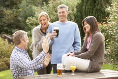 group of friends outdoors enjoying drink in pub garden - stock photo