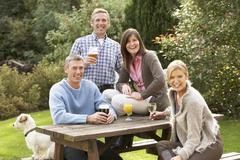 Group of friends outdoors enjoying drink in pub garden Stock Photos