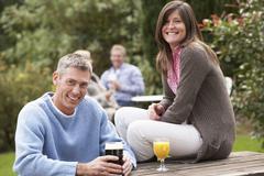 Couple outdoors enjoying drink in pub garden Stock Photos