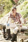 Woman with dog having coffee break whilst working outdoors in garden Stock Photos