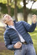 man listening to mp3 whilst walking in autumn park - stock photo
