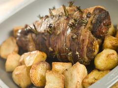 Roast Leg of Lamb Studded with Garlic and Rosemary and Roast Potatoes - stock photo