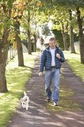 man walking dog outdoors in autumn park - stock photo