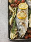Whole Sea Bass Roasted with Fennel Lemon Garlic and Cherry Tomatoes on the Vine - stock photo