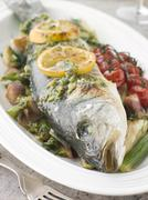 Whole Roasted Sea Bass with Fennel Lemon Cherry Vine Tomatoes and Salsa Verde - stock photo