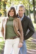 portrait of romantic couple enjoying outdoor walk through autumn park - stock photo