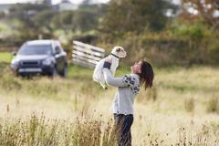 Young woman outdoors in autumn landscape holding dog Stock Photos