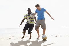 two young men palying football on beach together - stock photo