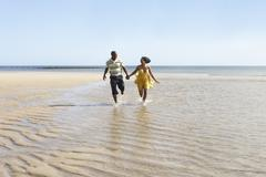 romantic young couple running along shoreline of beach holding hands - stock photo