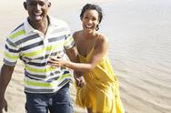 Stock Photo of romantic young couple running along shoreline of beach holding hands