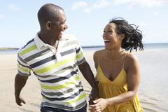 Romantic young couple running along shoreline of beach holding hands Stock Photos