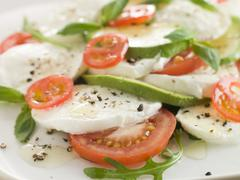 Tomato Avocado and Mozzarella Salad with Olive Oil and Black Pepper Stock Photos