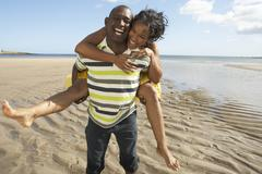 Young man giving woman piggyback along shoreline of beach Stock Photos