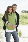 romantic young couple standing by dunes with beach hut in distance - stock photo