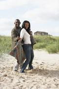 Stock Photo of romantic young couple standing by dunes with beach hut in distance