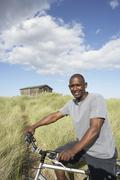 Young man riding mountain bike by dunes with old beach hut in distance Stock Photos