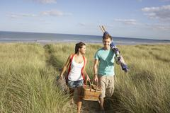 young couple carrying picnic basket and windbreak walking through dunes - stock photo