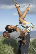 energetic young couple having fun in dunes by beach - stock photo