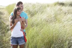 romantic young couple standing amongst dunes - stock photo