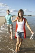 romantic young couple walking along shoreline of beach holding hands - stock photo