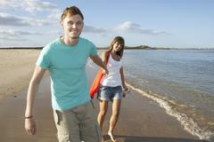Romantic young couple walking along shoreline of beach holding hands Stock Photos