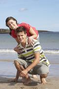 affectionate teenage couple having fun on beach - stock photo