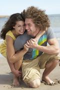 Affectionate young couple having fun on beach Stock Photos