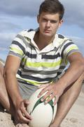teenage boy sitting on beach holding rugby ball - stock photo