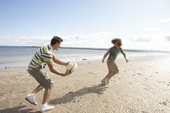two teenage boys playing rugby on beach together - stock photo