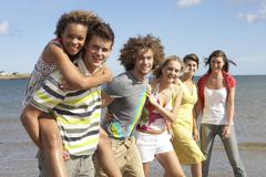 group of young friends walking along summer shoreline - stock photo