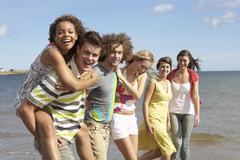 Group of young friends walking along summer shoreline Stock Photos
