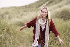 Teenage girl walking through sand dunes wearing warm clothing Stock Photos