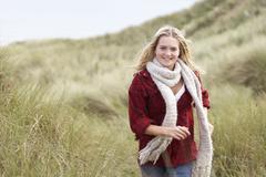 teenage girl walking through sand dunes wearing warm clothing - stock photo