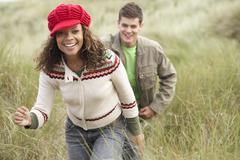 Teenage couple walking through sand dunes wearing warm clothing Stock Photos