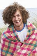Young man standing in sand dunes wrapped in blanket Stock Photos