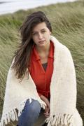 Young woman standing in sand dunes wrapped in blanket Stock Photos