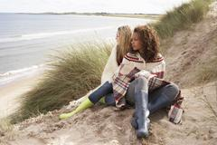 two teenage girls sitting in sand dunes wrapped in blanket - stock photo