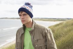 teenage boy standing in sand dunes wearing woolly hat - stock photo