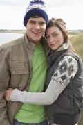 young couple walking through sand dunes wearing warm clothing - stock photo