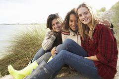 Three teenage girls sitting in sand dunes together Stock Photos