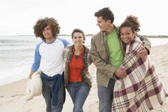 Group of young friends walking along autumn shoreline Stock Photos