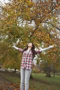 Teenage girl standing in autumn park with arms outstretched Stock Photos