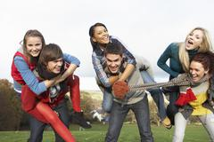 Stock Photo of group of teenage friends having piggyback rides in autumn landscape