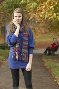 Unhappy teenage girl standing in autumn park with couple on bench in backgrou Stock Photos