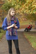 unhappy teenage girl standing in autumn park with couple on bench in backgrou - stock photo